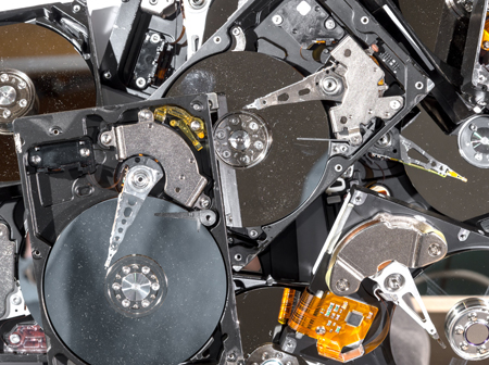 A pile of old computer hard drives which contain personal or business data that Green Ewaste Recycling Center can securely delete or physically destroy with Data Destruction