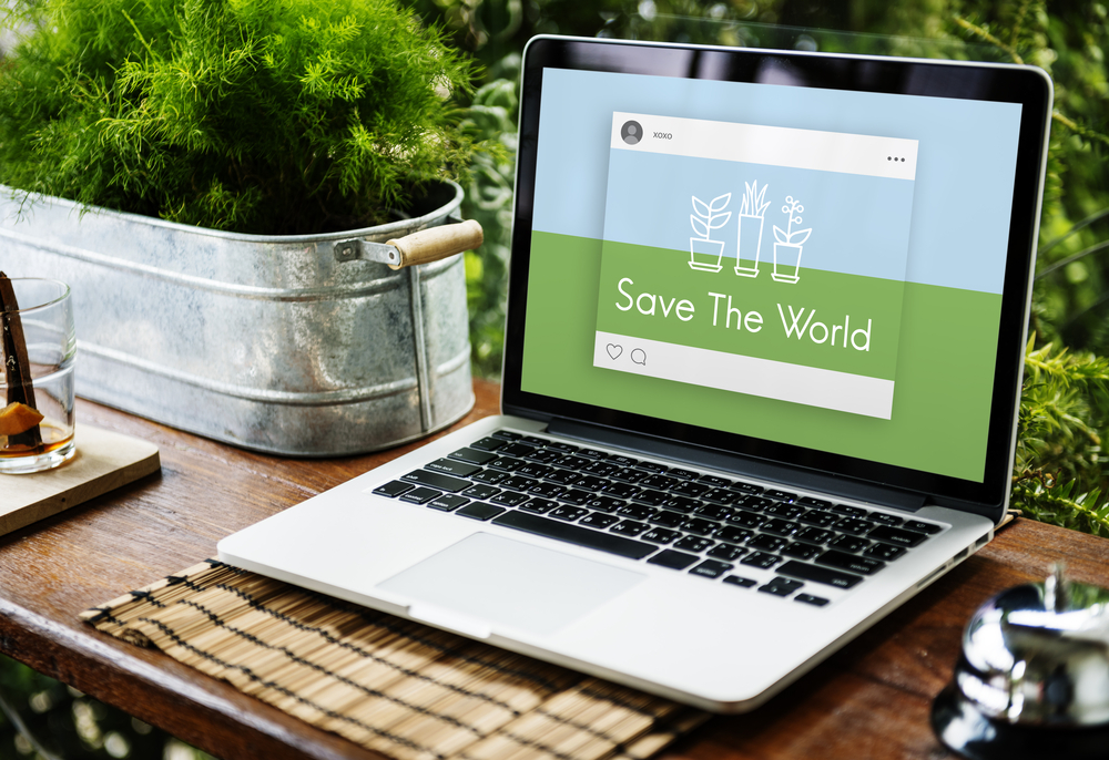 A laptop with an open screen showing an image that says save the world and is positioned next to a green plant to illustrate how laptop recycling can help the environment stay green.